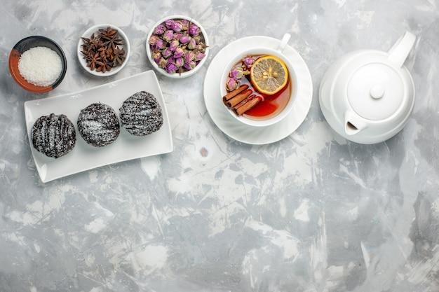 Bovenaanzicht heerlijke kleine cakes met suikerglazuur en kopje thee op licht-witte achtergrond thee koekje cake bakken suiker zoete taartkoekjes