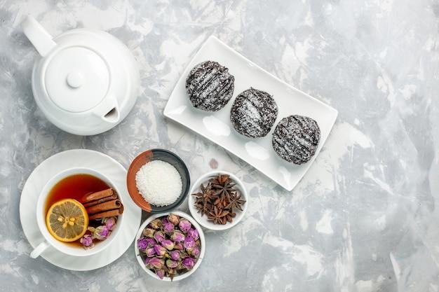 Bovenaanzicht heerlijke kleine cakes met suikerglazuur en kopje thee op licht-witte achtergrond thee koekje cake suiker zoete taartkoekjes