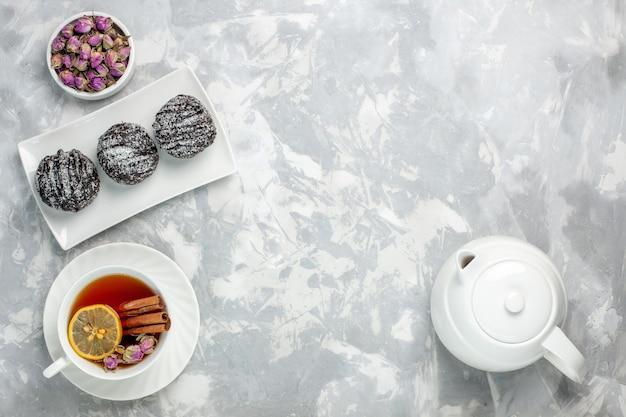 Bovenaanzicht heerlijke kleine cakes met suikerglazuur en kopje thee op wit bureau thee koekje cake bakken suiker zoete taart