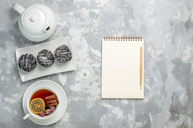 Bovenaanzicht heerlijke kleine cakes met suikerglazuur en kopje thee op witte achtergrond thee koekje cake bakken suiker zoete taartkoekjes