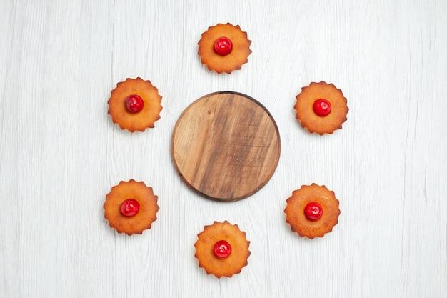Bovenaanzicht heerlijke kleine cakes op wit bureau