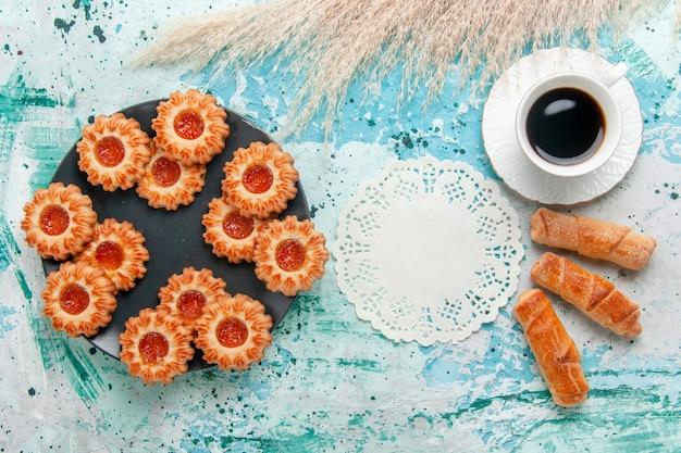 Bovenaanzicht heerlijke kleine koekjes met bagels en kopje koffie op blauw bureau koekjes biscuit zoete suiker kleur thee