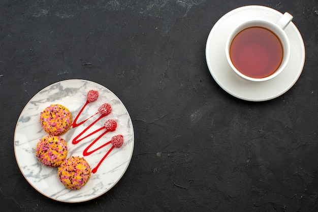 Bovenaanzicht heerlijke kleine koekjes met kopje thee op de grijze ruimte