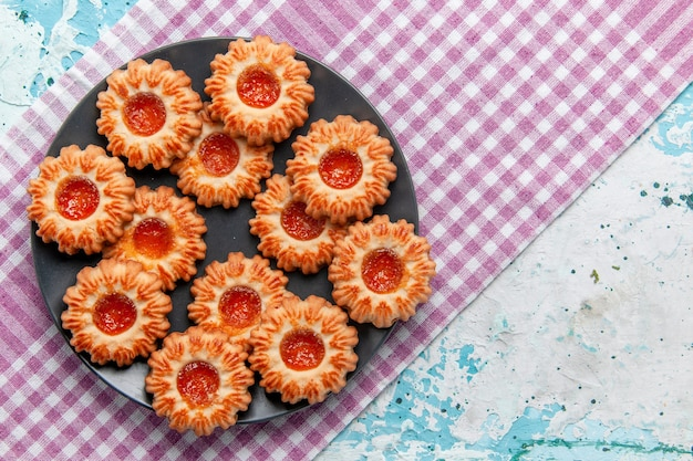 Bovenaanzicht heerlijke kleine koekjes met sinaasappeljam op de blauwe thee van de het koekjeskoekje zoete suiker van het bureau