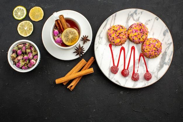 Bovenaanzicht heerlijke kleine koekjes met thee en kaneel op grijze ruimte