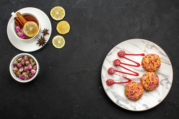 Bovenaanzicht heerlijke kleine koekjes met thee op grijze ruimte