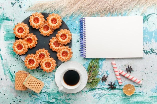 Bovenaanzicht heerlijke kleine koekjes met wafels en kopje koffie op het blauwe bureau koekjeskoekje zoete suiker kleur thee