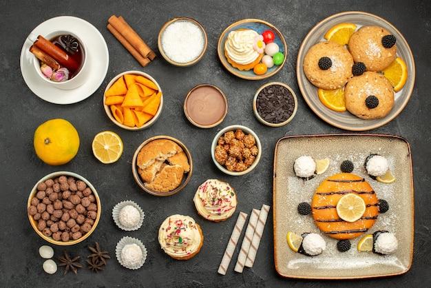 Bovenaanzicht heerlijke kleine taart met koekjes, chips en kopje thee op grijs oppervlak cake thee biscuit koekje zoet