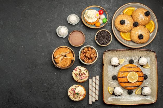 Bovenaanzicht heerlijke kleine taart met koekjes, chips en kopje thee op grijze achtergrond cake thee biscuit koekjes zoet
