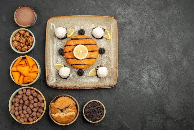Bovenaanzicht heerlijke kleine taart met kokos snoepjes op een donkergrijze achtergrond biscuit taart taart koekjes snoep zoet