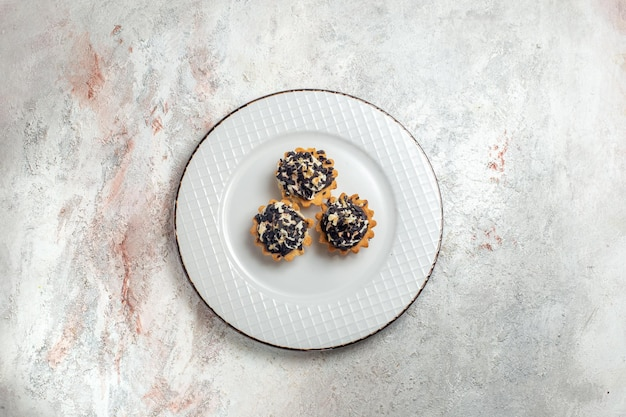 Bovenaanzicht heerlijke kleine taarten met chocoladeschilfers in plaat op witte achtergrond cake biscuit zoete cream tea dessert