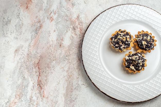 Bovenaanzicht heerlijke kleine taarten met chocoladeschilfers in plaat op witte achtergrond thee cake biscuit zoete room dessert