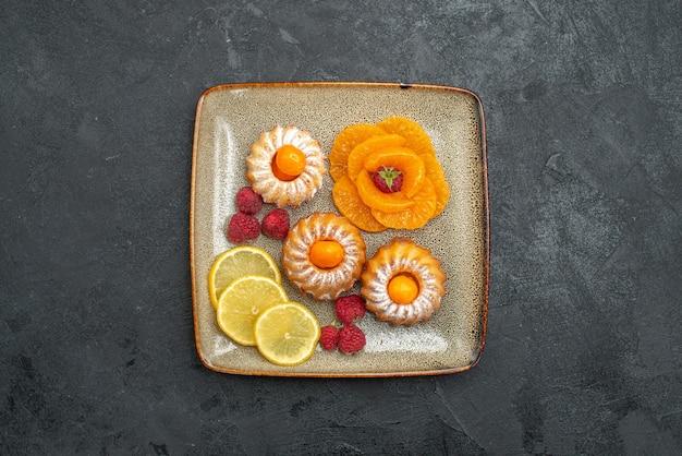 Bovenaanzicht heerlijke kleine taarten met schijfjes citroen en mandarijnen op de donkere achtergrond, fruitkoekje, zoete theekoekje