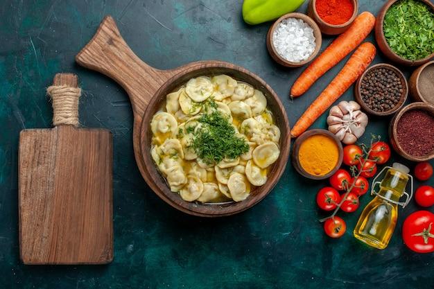 Bovenaanzicht heerlijke knoedels met groenten en verschillende smaakmakers op donkergroen bureau maaltijd voedselingrediënt product deeg vlees