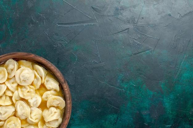Bovenaanzicht heerlijke knoedelsoep in bruine plaat op donkergroen bureau eten deeg groentesoep vlees