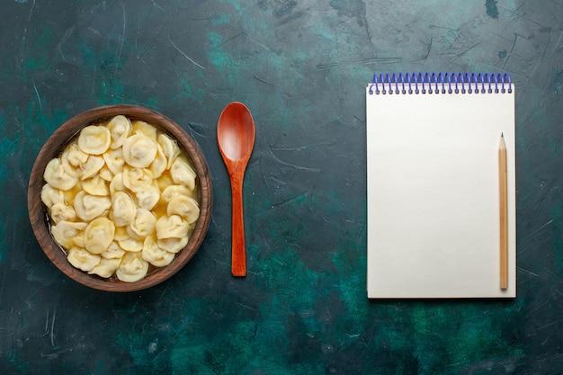 Bovenaanzicht heerlijke knoedelsoep in bruine plaat op een donkergroen bureau eten vlees groentesoepdeeg