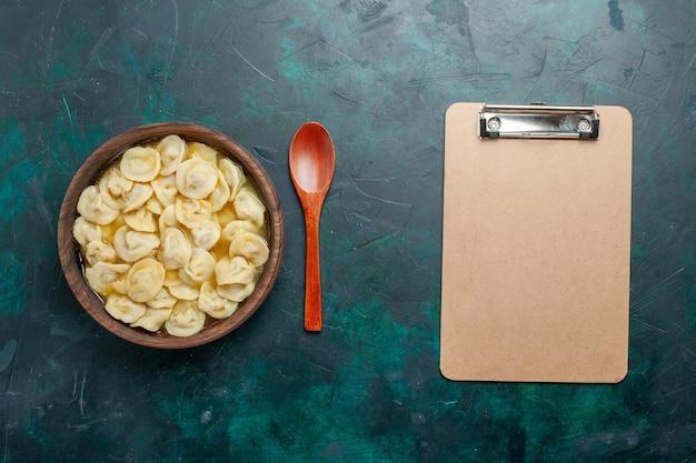 Bovenaanzicht heerlijke knoedelsoep in bruine plaat op een donkergroene achtergrond voedsel vlees groentesoep deeg