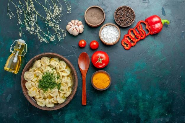 Bovenaanzicht heerlijke knoedelsoep met oliekruiden en tomaten op het groene vlees van het de soepdeeg van de achtergrondvoedselmaaltijd