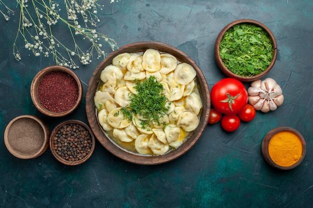 Bovenaanzicht heerlijke knoedelsoep met verschillende kruiden op een donkergroene ondergrond vlees groente voedseldeeg soep