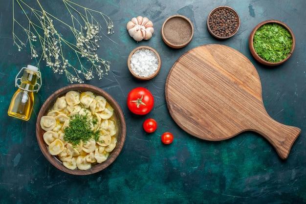 Bovenaanzicht heerlijke knoedelsoep met verschillende kruiden op het groene oppervlak, soep, groenten, deeg, vlees