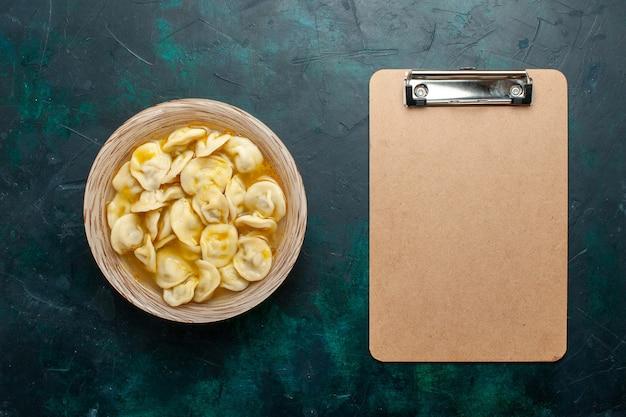 Bovenaanzicht heerlijke knoedelsoep op donkergroene achtergrond voedseldeeg groenten soepvlees