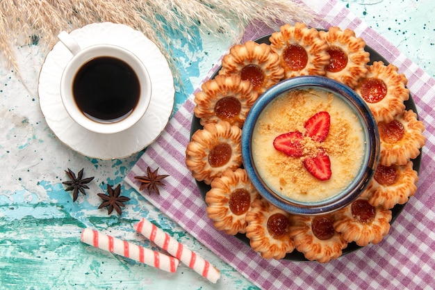 Bovenaanzicht heerlijke koekjes met aardbeiendessert en koffie op blauwe ondergrond