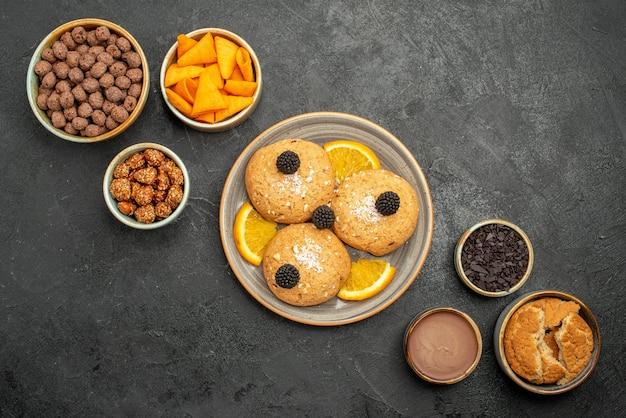 Bovenaanzicht heerlijke koekjes met chips en noten op donkergrijs oppervlak koekjeskoekjes thee zoete cake