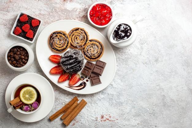 Bovenaanzicht heerlijke koekjes met chocoladetaart en thee op lichte ruimte