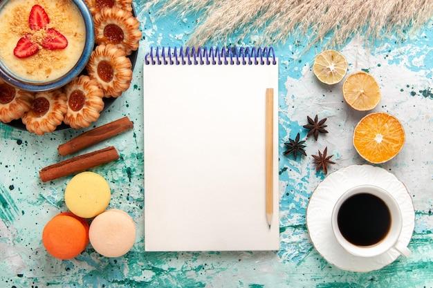 Bovenaanzicht heerlijke koekjes met franse macarons aardbeiendessert en kopje koffie op blauwe ondergrond