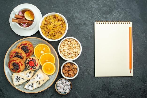 Bovenaanzicht heerlijke koekjes met fruitige gebakjes, sinaasappelthee en noten op donkere oppervlakte, notensnackthee, zoete snoepjes