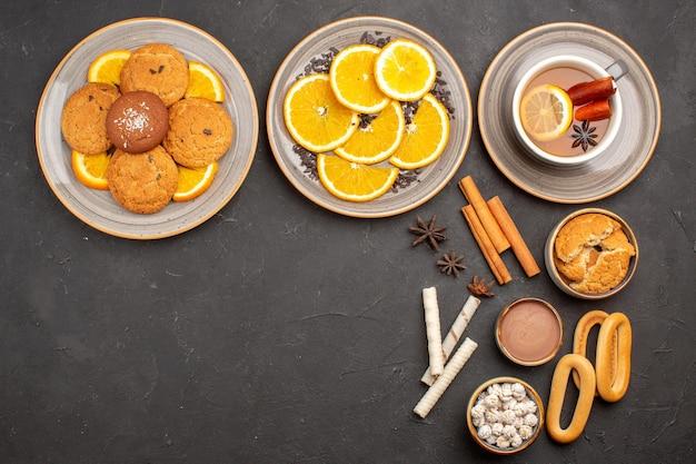 Bovenaanzicht heerlijke koekjes met gesneden sinaasappels en kopje thee op donkere achtergrond suikerkoekje fruit zoet koekje