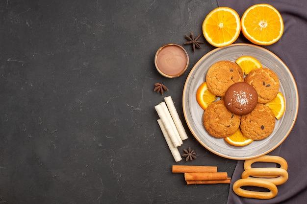 Bovenaanzicht heerlijke koekjes met gesneden sinaasappels op donkere achtergrond suikerkoekje dessertkoekje zoet