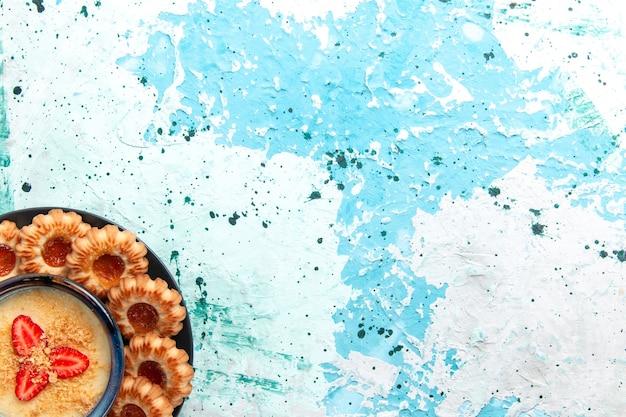 Bovenaanzicht heerlijke koekjes met jam en aardbeidessert op de lichtblauwe cake van het de koekjessuiker zoete koekje