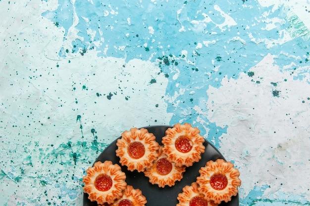 Bovenaanzicht heerlijke koekjes met jam in zwarte plaat op lichtblauw bureau cookie biscuit zoete suiker kleur thee