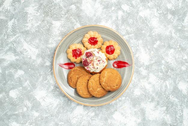 Bovenaanzicht heerlijke koekjes met koekjes en slagroomtaart op een wit bureau, zoete koekjeskoekjes, suikertheecake