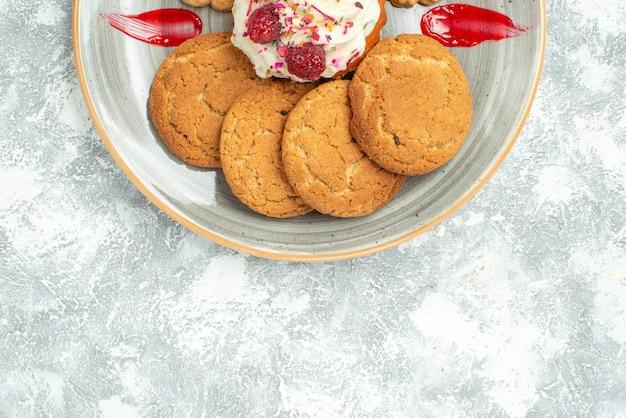 Bovenaanzicht heerlijke koekjes met koekjes en slagroomtaart op wit bureau, zoete koekjeskoekjes, suikertheecake