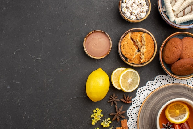 Bovenaanzicht heerlijke koekjes met kopje thee en citroen op donkere oppervlaktekoekje zoete citruskoekje fruitsuiker