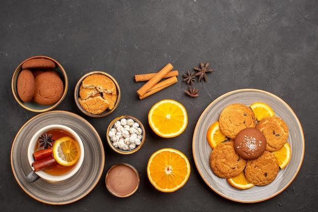 Bovenaanzicht heerlijke koekjes met kopje thee en gesneden sinaasappels op donkere oppervlakte suikerkoekje dessertkoekje zoet