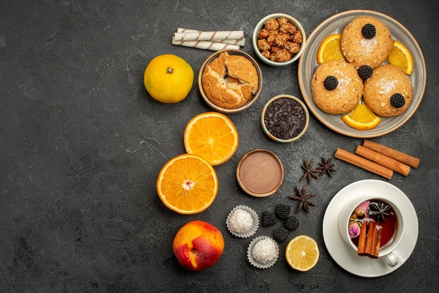 Bovenaanzicht heerlijke koekjes met kopje thee en sinaasappel op donkere oppervlakte theekoekjeskoekjescake