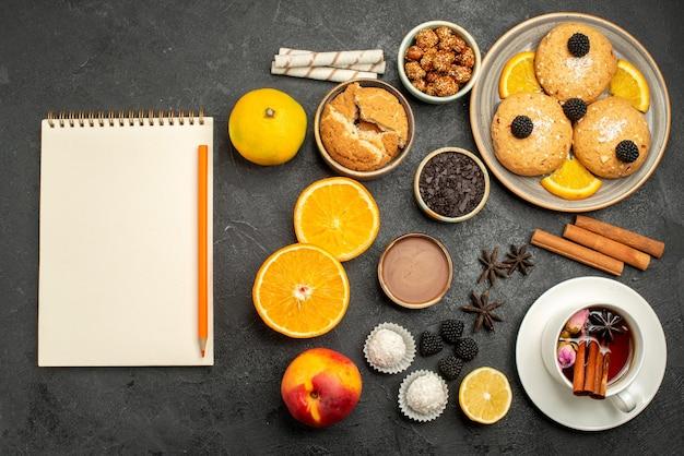 Bovenaanzicht heerlijke koekjes met kopje thee en stukjes sinaasappel op donkere theekoekjeskoekjeskoekjes