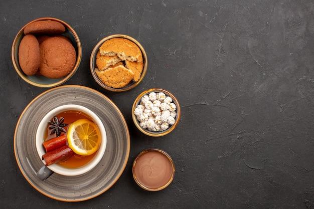 Bovenaanzicht heerlijke koekjes met kopje thee op donkere oppervlakte suikerkoekje dessertkoekje zoet