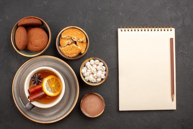 Bovenaanzicht heerlijke koekjes met kopje thee op donkere oppervlakte suikerkoekjes dessertkoekje zoet