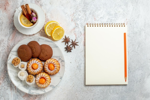 Bovenaanzicht heerlijke koekjes met kopje thee op witte achtergrond cookie biscuit suiker zoete cake thee