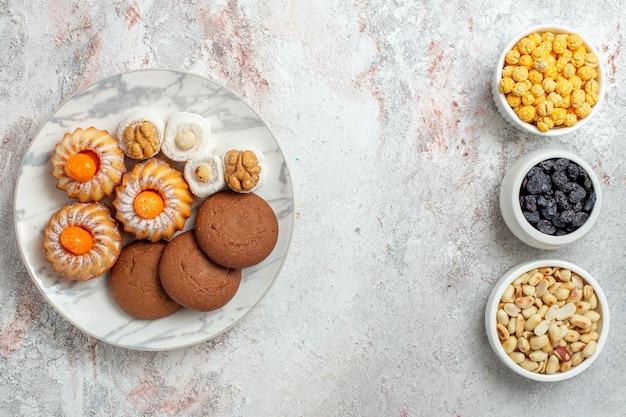 Bovenaanzicht heerlijke koekjes met noten en rozijnen op witte achtergrond notenkoekje zoete cake suiker