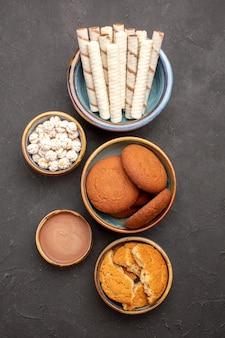 Bovenaanzicht heerlijke koekjes met pijpkoekjes op donkere oppervlakte suikerkoekje dessertkoekje zoet