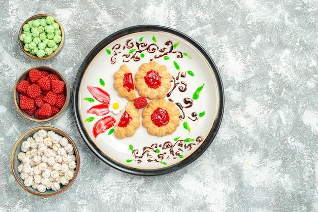 Bovenaanzicht heerlijke koekjes met rode gelei en snoepjes op lichte witte achtergrond biscuit cake cookie zoete thee