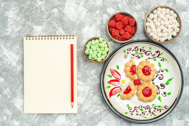 Bovenaanzicht heerlijke koekjes met rode gelei en snoepjes op witte achtergrond biscuit cake cookies sweet