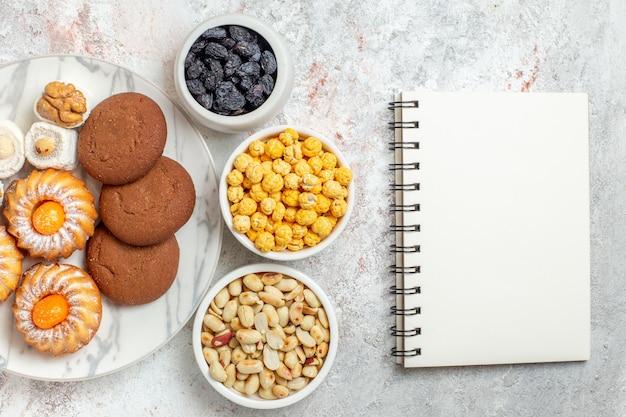 Bovenaanzicht heerlijke koekjes met snoep en noten op witte achtergrond zoete cake cookie biscuit suiker thee