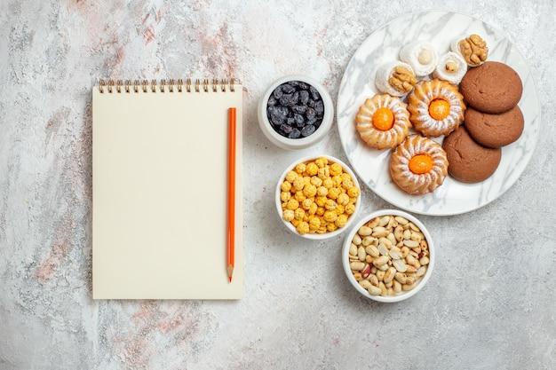 Bovenaanzicht heerlijke koekjes met snoep op witte achtergrond cookie biscuit zoete cake suiker thee