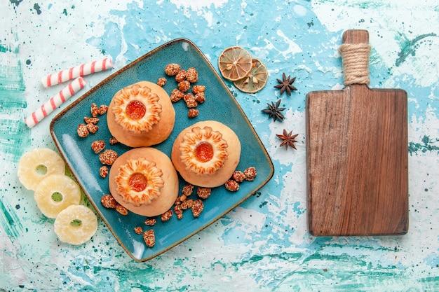 Bovenaanzicht heerlijke koekjes met snoepjes op blauwe achtergrond koekjeskoekje zoete suikerkleur